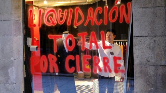 Un hombre se prueba una camisa en una tienda de Barcelona que anuncia su liquidación por cierre