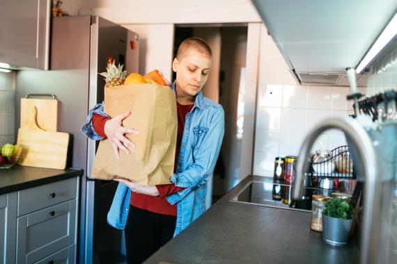 Una mujer llega a la cocina con la compra de casa.