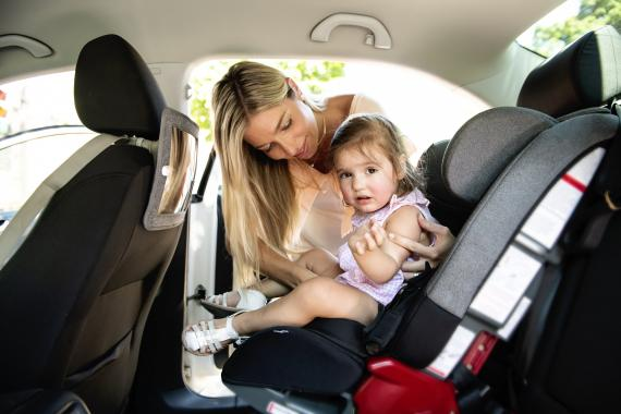 Una mujer sienta a su hija en el coche