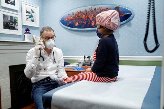 Un pediatra atendiendo a una niña