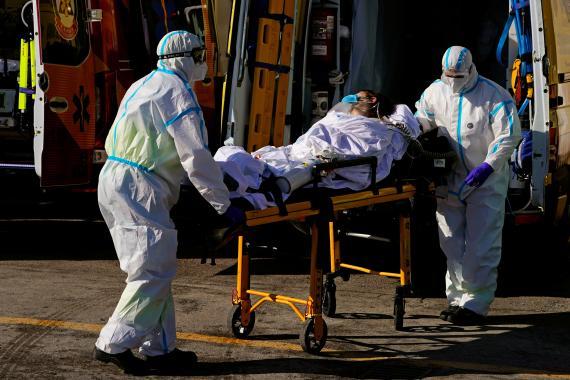 Sanitarios llevan a un paciente con COVID-19 en una camilla a la ambulancia.