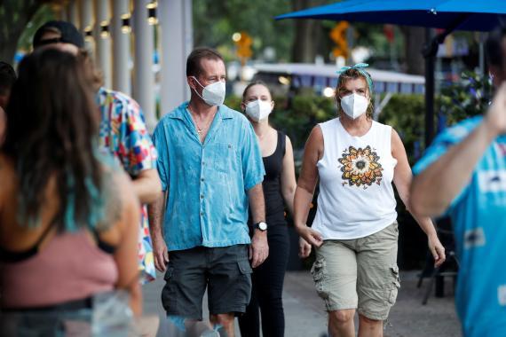 Turistas andando por la calle con mascarilla.