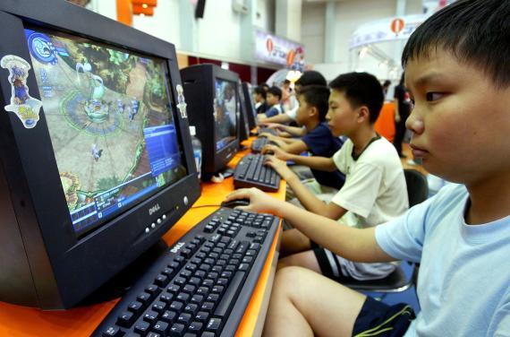 Un niño chino juega a un videojuego en el ordenador.