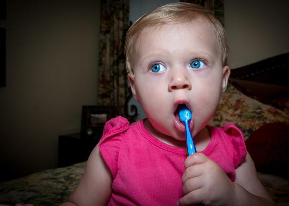 Un bebé con un cepillo de dientes en la boca.
