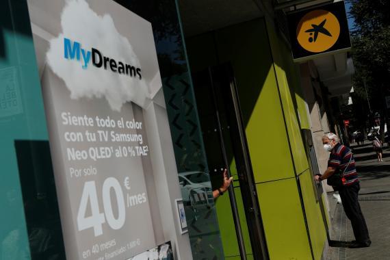 Un cliente de Bankia usa un cajero en una sucursal de CaixaBank.