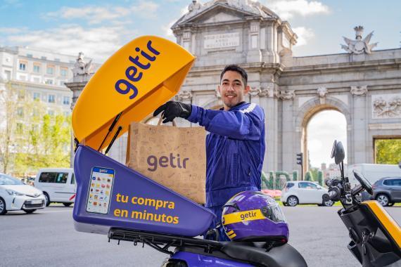 Un repartidor de Getir vestido con los colores corporativos de la compañía; el morado y amarillo.