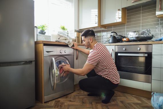 Un hombre poniendo la lavadora