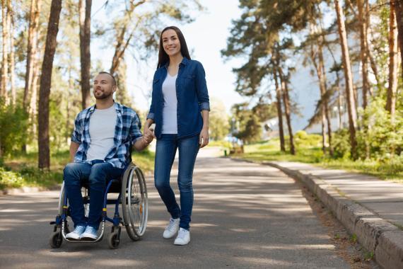 Un hombre en silla de ruedas pasea con su pareja