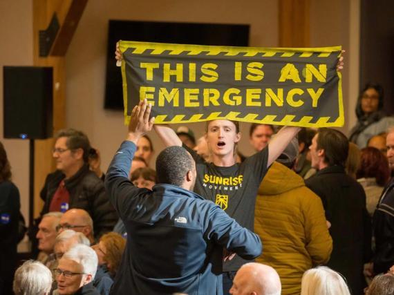 Manifestantes contra la emergencia climática interrumpen al entonces candidato Joe Biden durante un evento de campaña en New Hampshire en 2019. El Movimiento Sunrise se autodenomina un movimiento juvenil centrado en prevenir el cambio climático.