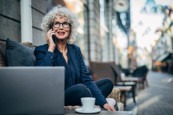 mujer madura con canas toma tomando café