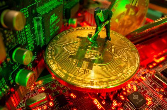 El muñeco de un minero encima de una moneda de bitcoin.