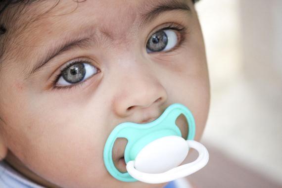 Una niña con chupete y los ojos muy abiertos.