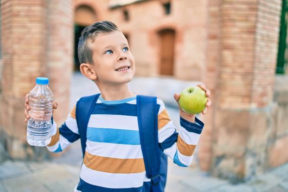 niño mochila comienzo manzana