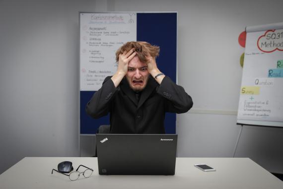 Una persona con cara de susto mirando el ordenador.
