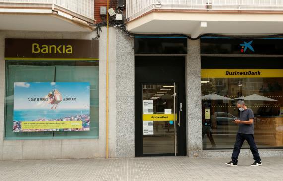 Un hombre pasa por unos cajeros de CaixaBank y Bankia
