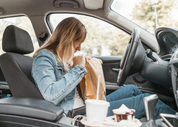 mujer comiendo comida basura en el coche