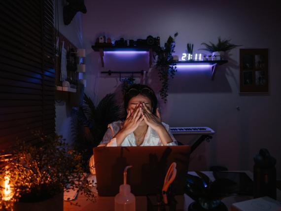 Una mujer exhausta delante del ordenador mientras trabaja.