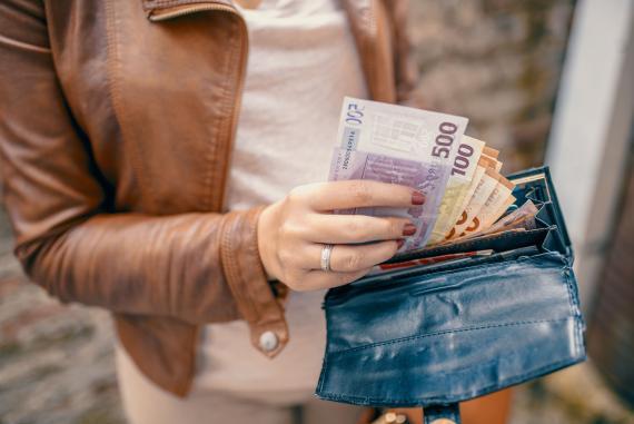 Una mujer sacando dinero en efectivo de la cartera