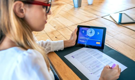 Una mujer trabaja en una tablet con el símbolo de Ethereum.