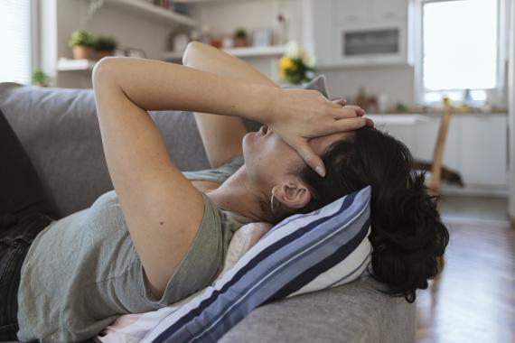Persona enferma, en el sofá, cansada.
