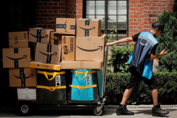 Un repartidor carga varios paquetes de Amazon