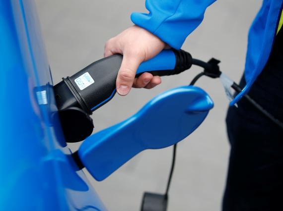 Persona cargando un coche eléctrico