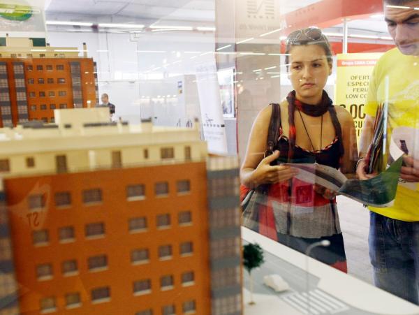 Una pareja observa la maqueta de un bloque de edificios en una feria de vivienda