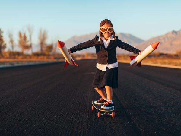 Una niña monta en patinete en una pista de aviones