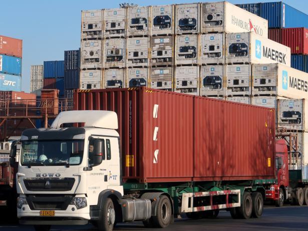 Un camión transporta un contenedor logístico en el puerto de Tianjin (China)