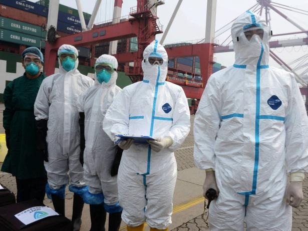 Investigadores lidian con un supuesto paciente del Síndrome Respiratorio de Oriente Medio (MERS) en un puerto marítimo el 18 de junio de 2015 en Qingdao, China.