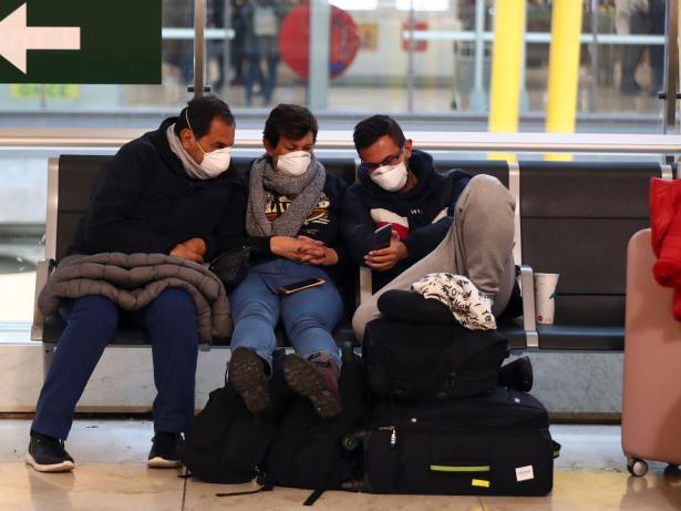 Tres hombres miran su teléfono móvil en el aeropuerto de Barajas.