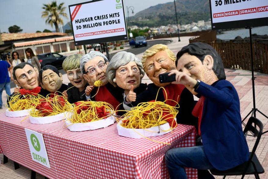 Una protesta con máscaras de los líderes de los países del GT posan para un selfi durante una protesta en Giardini Naxos, en Sicilia (Italia).