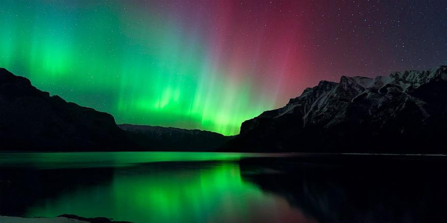 La aurora boreal es una muestra visible de partículas atómicas cargadas eléctricamente procedentes del Sol que interactúan con el campo magnético de la Tierra.