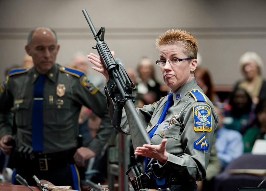 La detective Barbara J. Mattson sostiene un rifle Bushmaster AR-15, la misma marca y modelo de arma usada en el tiroteo de la Escuela Sandy Hook.