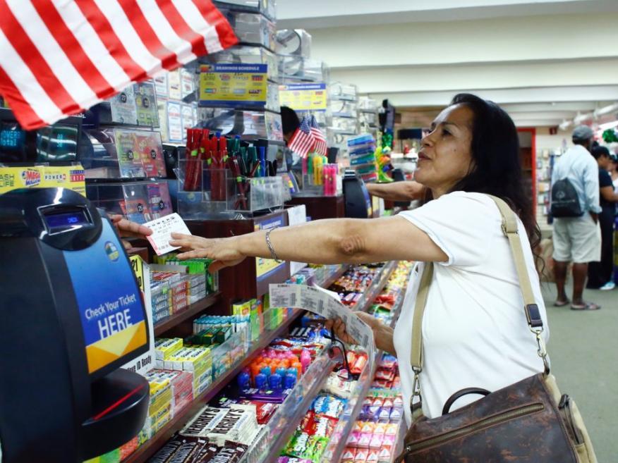 Una mujer compra un boleto de Powerball, juego de lotería americana.