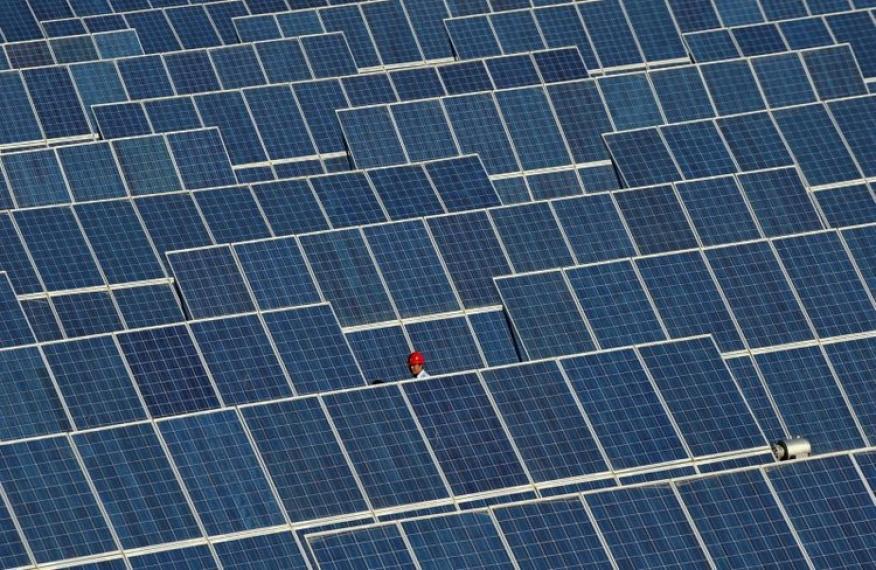 Un empleado camina entre los paneles de una central de energía solar en China.