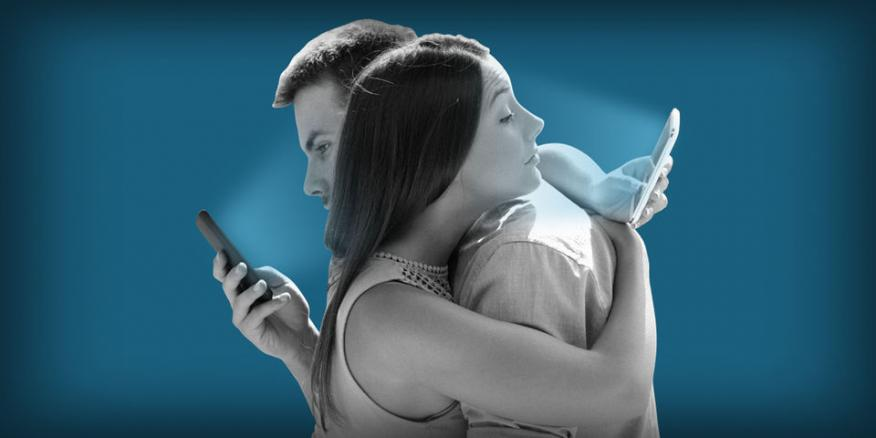 Pareja abrazada mirando móvil