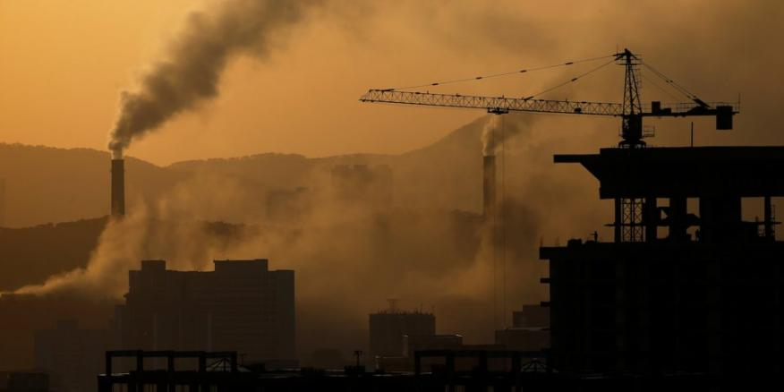 La gente trabaja en lo alto de un edificio en construcción mientras se pone el sol en Pyongyang, Corea del Norte,12 de abril de 2017