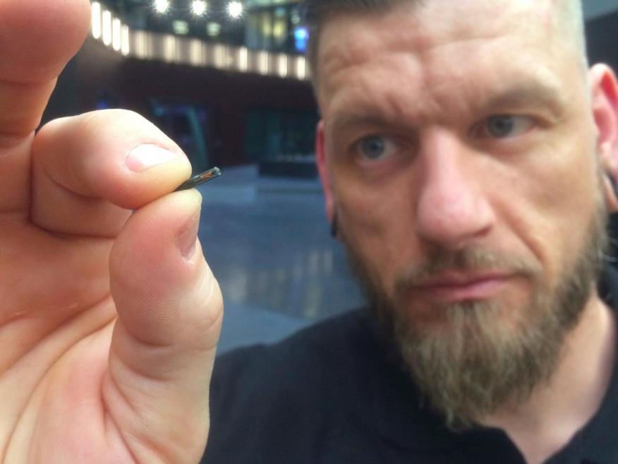 El microchip implantado es tan pequeño como un grano de arroz, como muestra la foto con el hacker de cuerpos Jowan Osterlund, de Biohax, Suecia.