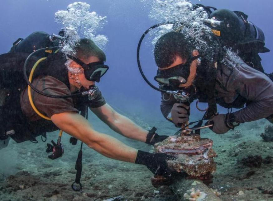 Buceadores eliminan ánodos de zinc corroídos de un cable submarino cerca de Hawaii.