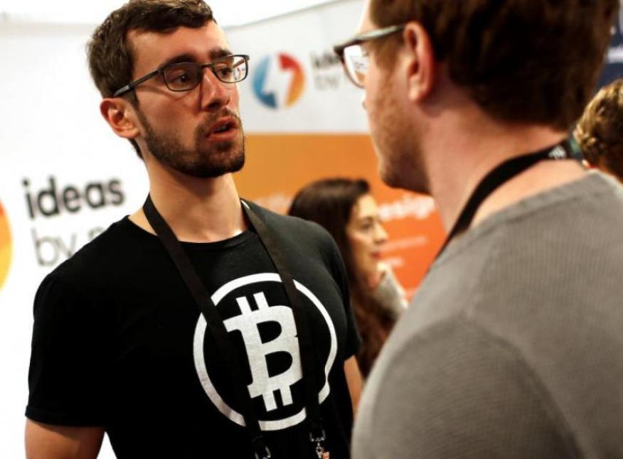 Un hombre lleva una camiseta con el logo de bitcoin en la Conferencia de Nueva York sobre la tecnología blockchain de 2018.