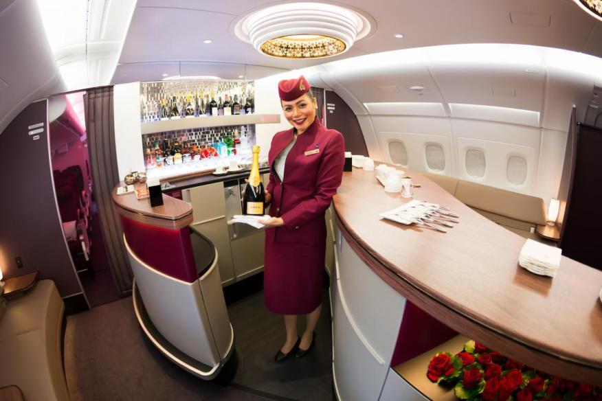 Una azafata te saluda al entrar en un avión de Qatar Airways.