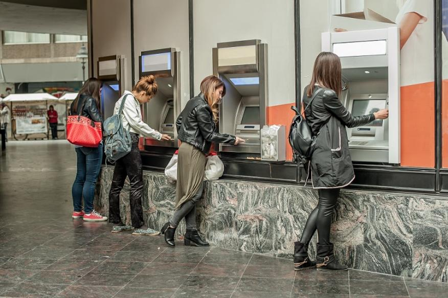 Personas sacando dinero de cajeros.