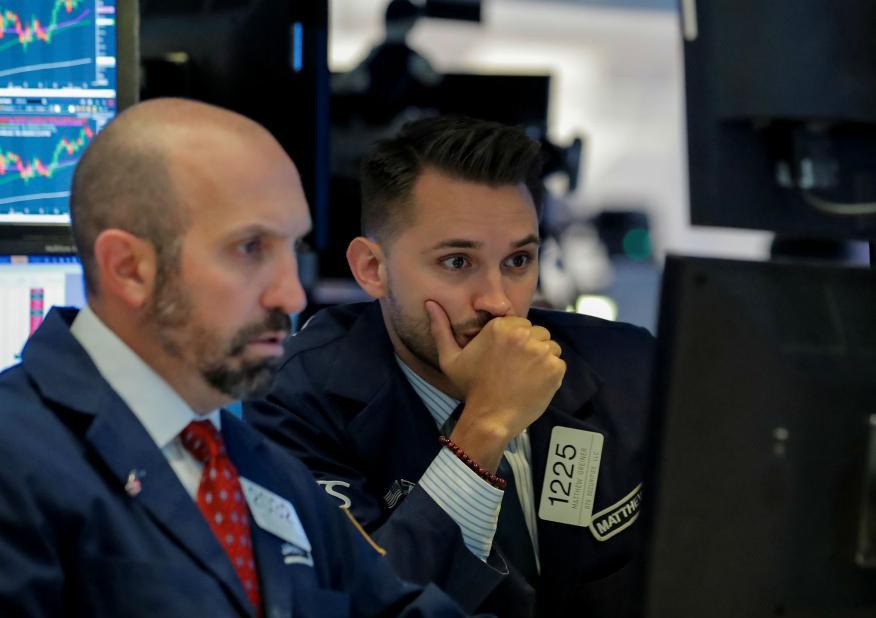 Dos traders en Wall Street mirando las pantallas de la cotización de la bolsa.