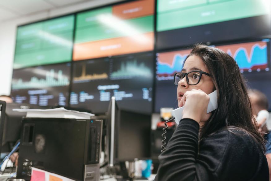 Una trader con las pantallas de los mercados de fondo.