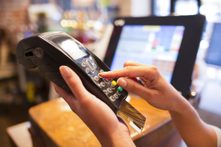 Un usuario paga con su tarjeta de crédito en un terminal de punto de venta