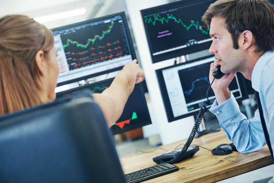 Dos economistas analizan varias pantallas con resultados económicos