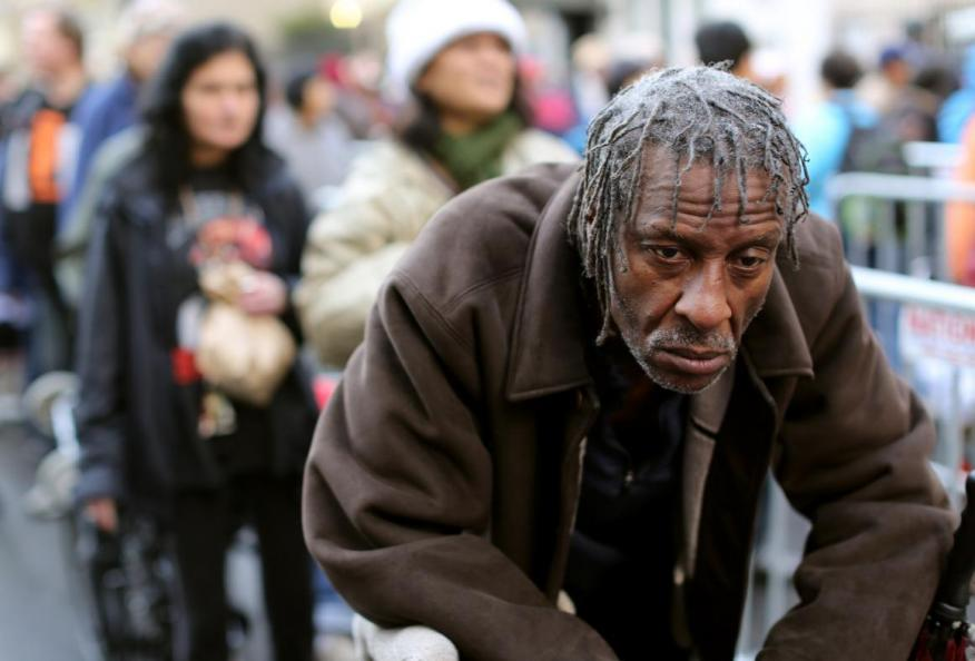A man waits in line for one of 5,000 holiday food bags in San Francisco's Tenderloin neighborhood.