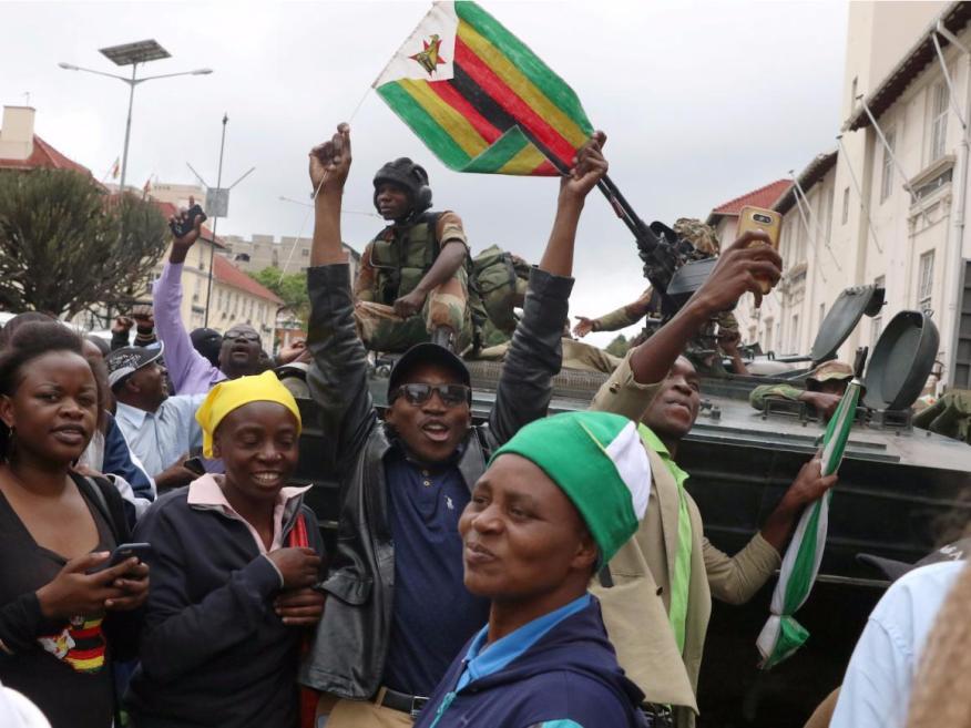 Manifestantes pidiendo al presidente zimbabuense Robert Mugabe que renuncie frente a un vehículo militar en Harare, en noviembre de 2017.