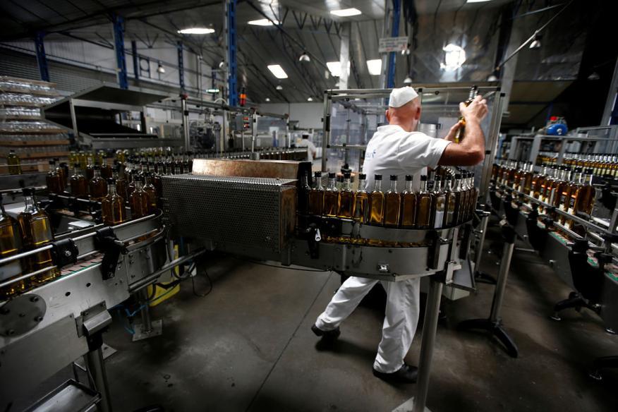 Un trabajador revisa una línea de embotellado de aceite de oliva en una planta de Dos Hermanas (Sevilla)